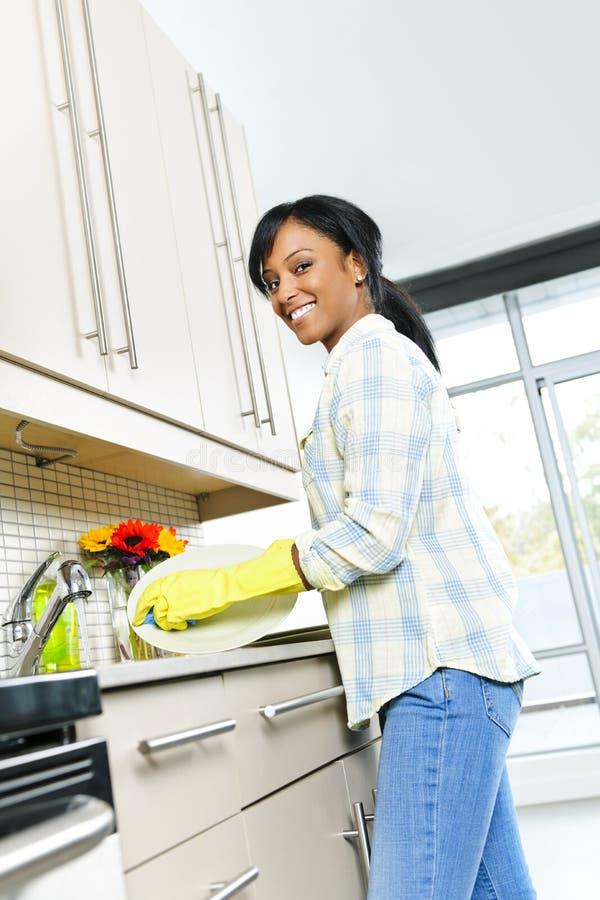Pratos de lavagem felizes da mulher nova fotografia de stock royalty free