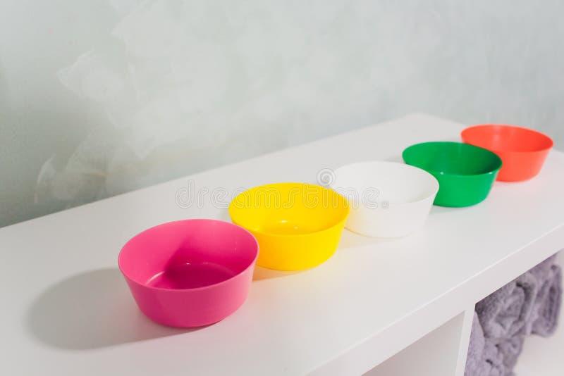 Pratos de plástico coloridos reutilizáveis na prateleira da loja foto de stock