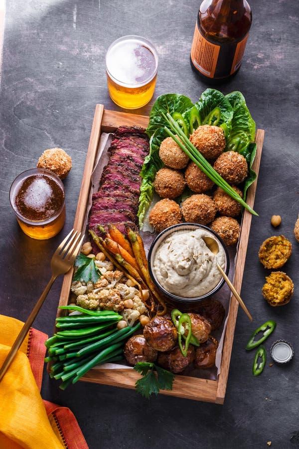 Pratos do Oriente Médio ou árabes e meze sortido em um fundo escuro Carne, falafel, ghanoush do babá, vegetais halal foto de stock royalty free