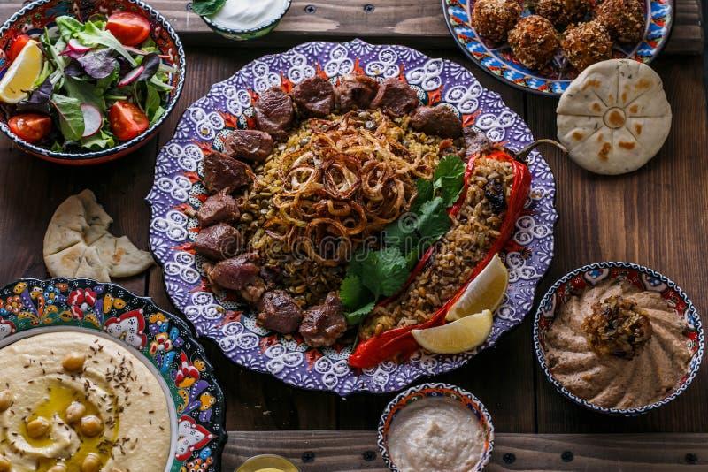 Pratos do Oriente Médio ou árabes: no espeto, falafel, hummus, arroz, tahini, kashke bademjan, pão árabe Vista superior imagens de stock royalty free