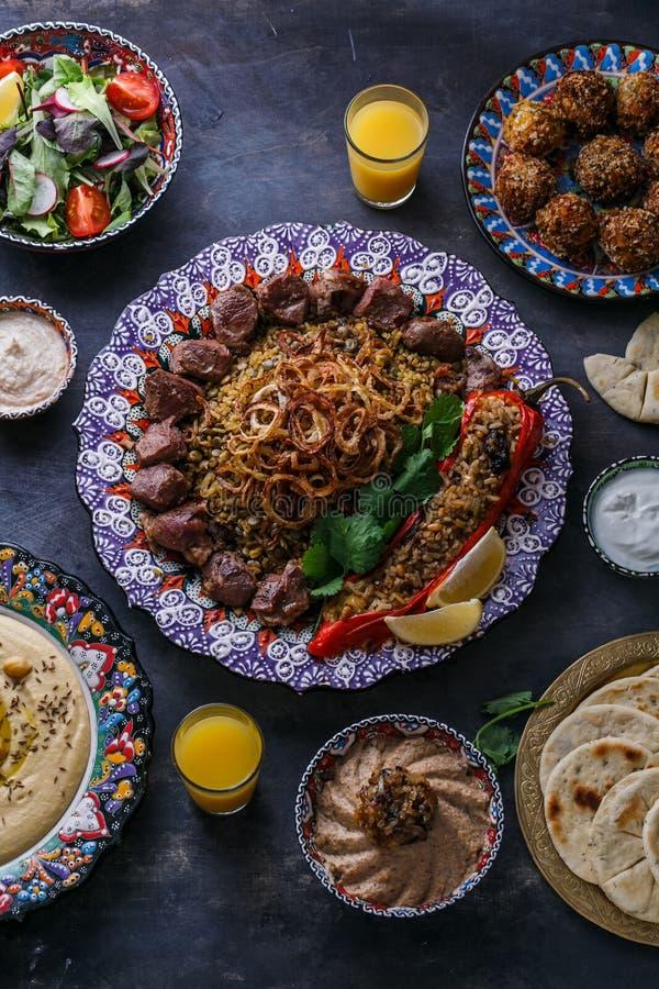 Pratos do Oriente Médio ou árabes: no espeto, falafel, hummus, arroz, tahini, kashke bademjan, pão árabe Vista superior imagem de stock