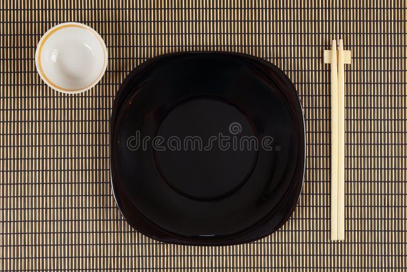 Pratos e hashis japoneses na esteira de bambu Vista de acima imagens de stock