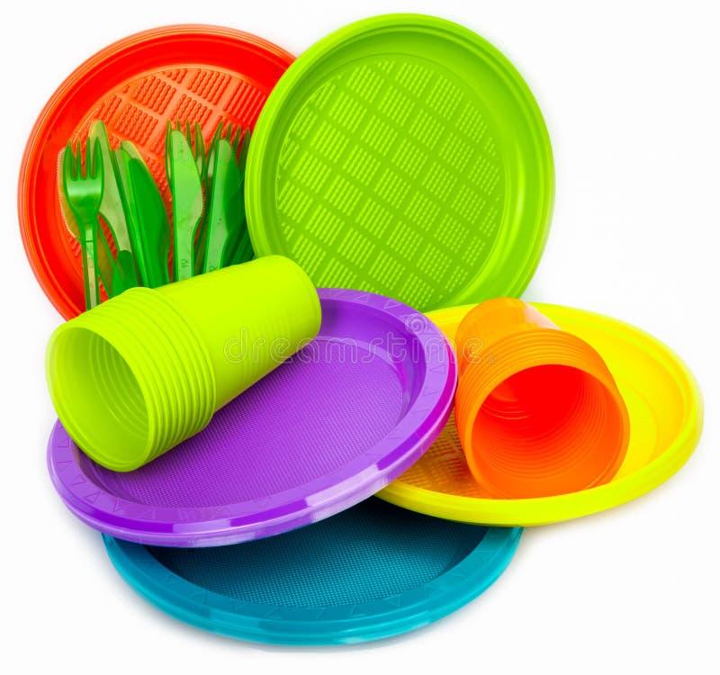 Pratos plásticos brilhantes descartáveis empilhados no branco foto de stock