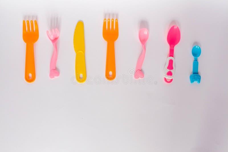 Pratos plásticos em um fundo branco, forquilhas das crianças, colheres, placa com espaço para o texto Configuração lisa, conceito ilustração stock