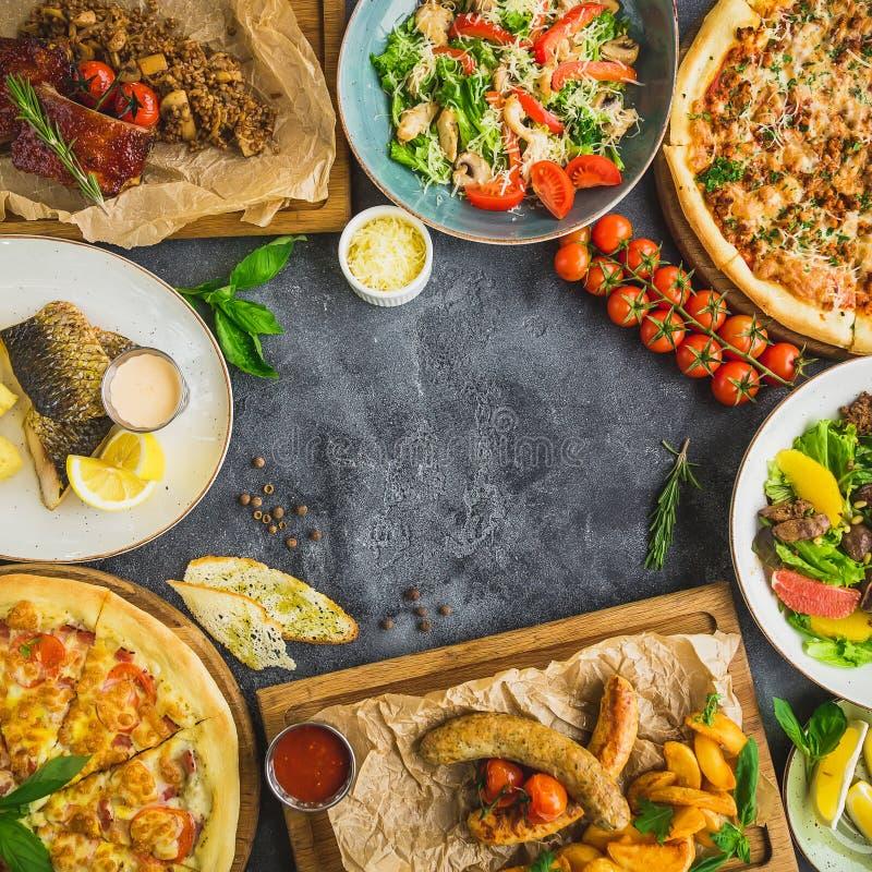 Pratos saborosos na tabela Reforços de carne de porco, pizza, saladas, peixes e salsichas grelhados com batatas fritadas Vista su imagem de stock