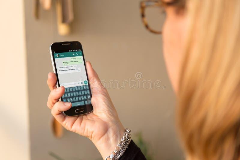 Pratstund av whatsappapplikationen i skärmen av mobiltelefonen Hög kvinna med smartphonen i hennes händer fotografering för bildbyråer