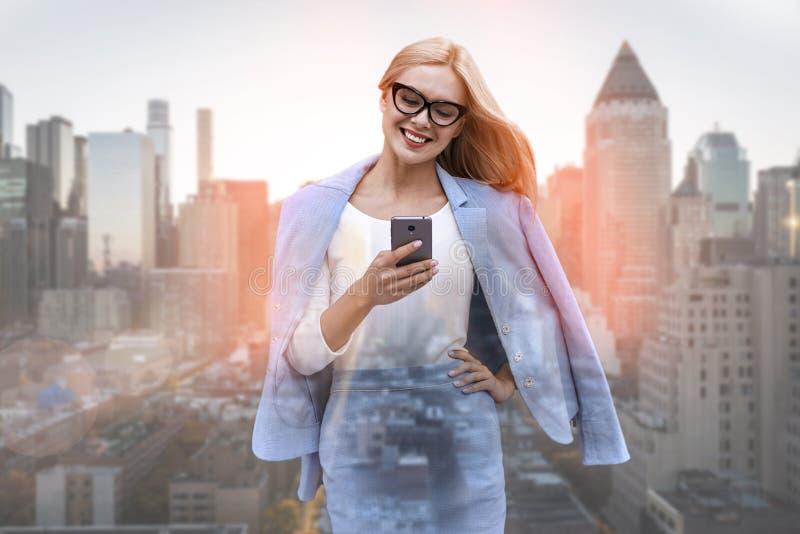 Pratstund med klienten Härlig ung affärskvinna i dräkt genom att använda den smarta telefonen och le, medan stå utomhus med arkivfoto