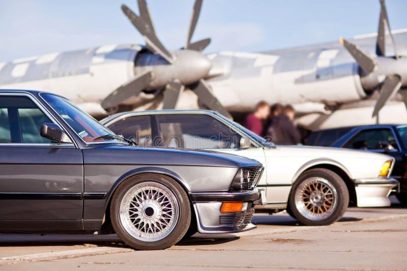 Prawa frontowa strona dwa starego europejskiego sportowego samochodu z samolotem na tle zdjęcie stock