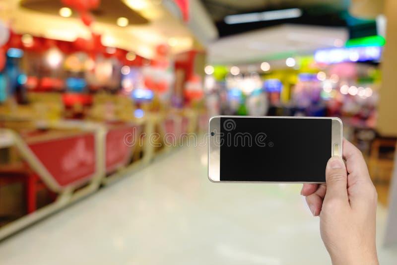 Prawa ręka używać mądrze telefon z pustym ekranem na abstrakcjonistycznej plamie obrazy stock