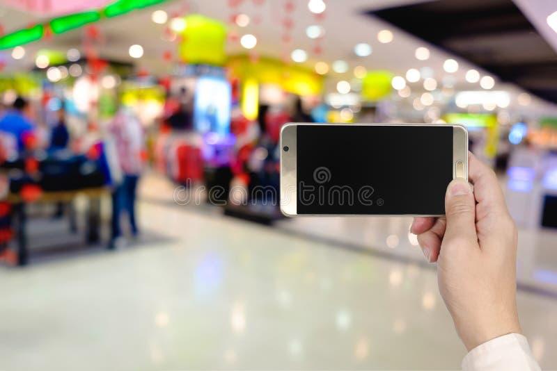 Prawa ręka używać mądrze telefon z pustym ekranem na abstrakcjonistycznej plamie zdjęcia stock