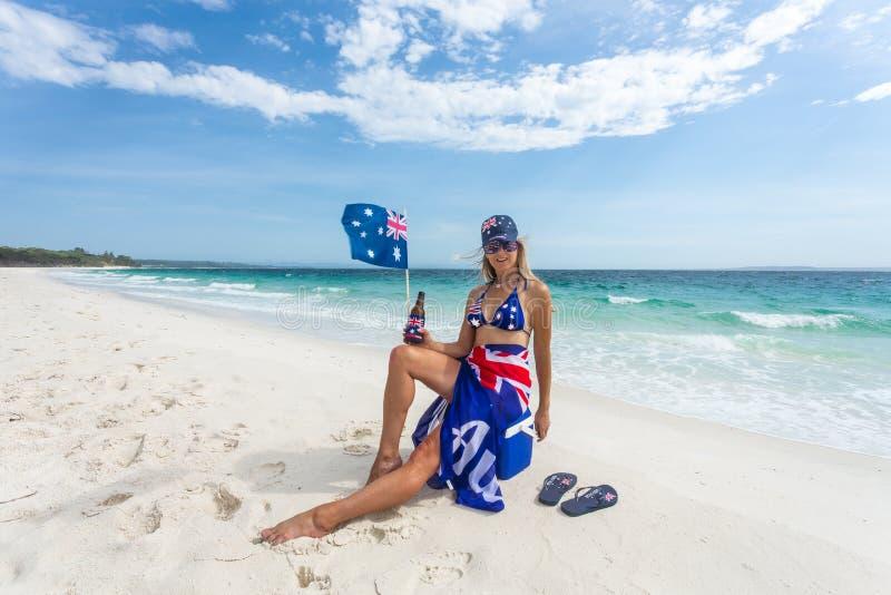 Prawdziwa Błękitna Uczciwa Dinkum Australijska dziewczyna kłaść z powrotem na plaży zdjęcie stock
