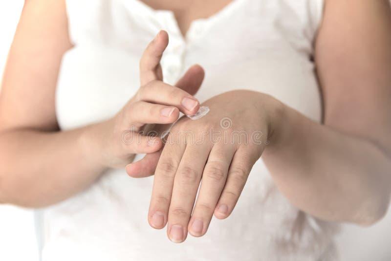 Prawdziwa kobieta naciera jej ręki z mistouriser płukanką przeciw białemu tłu zdjęcia stock