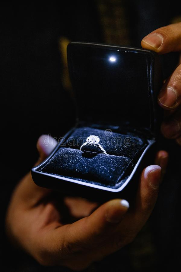 Prawdziwe życie propozycja: Mężczyzna trzyma iluminującego pierścionek zaręczynowego - Błękitny panna młoda pierścionek z dużym k obrazy royalty free