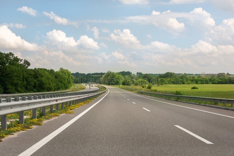 Prawie emty asfaltowa autostrada z błękitnym cloudys niebem na tle Autostrady płatnej budowa zdjęcie stock