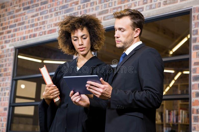 Prawnik patrzeje cyfrową pastylkę i oddziała wzajemnie z biznesmenem zdjęcie royalty free