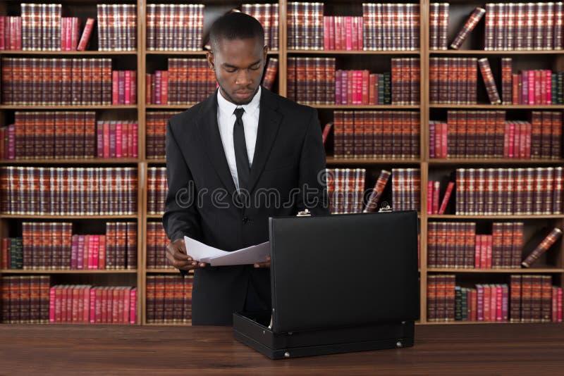 Prawnik Z papierami I teczką Przy biurkiem obraz stock
