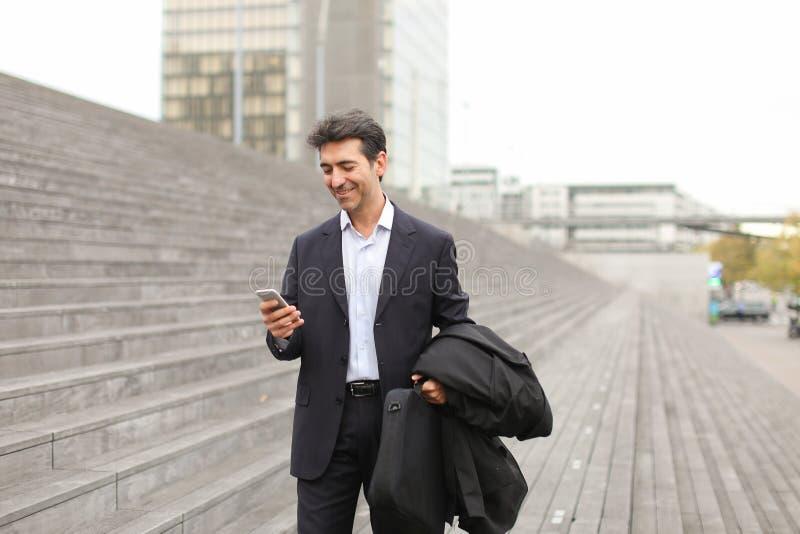 Prawnika mężczyzna w biznesu odzieżowym czekaniu dla klienta używać mądrze fotografia stock