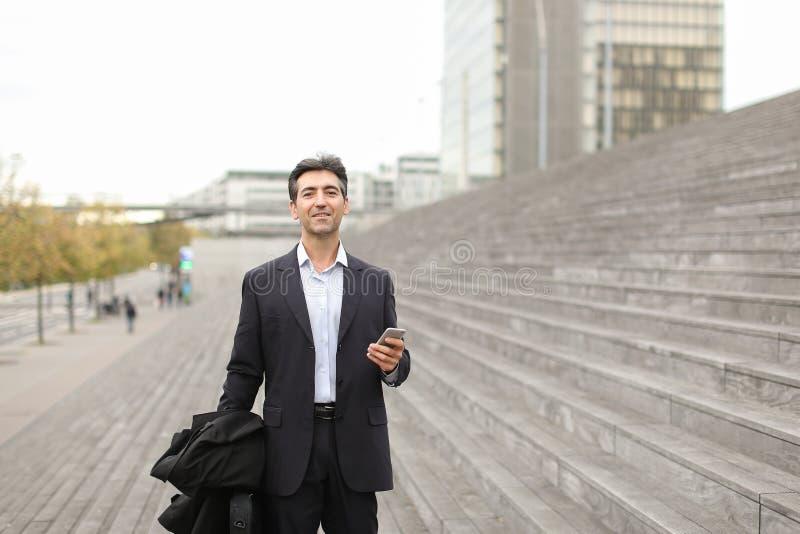 Prawnika mężczyzna w biznesu odzieżowym czekaniu dla klienta używać mądrze obraz stock