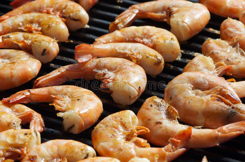 Prawns on the barbecue. Close up shot of green king prawns being grilled on a barbecue royalty free stock photos