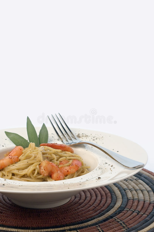 Prawns and Pasta series. Spaghetti and prawns in a cream sauce, garnished with herbs. Served on a deep white, round bowl with wide rim sprinkled with ground royalty free stock photography