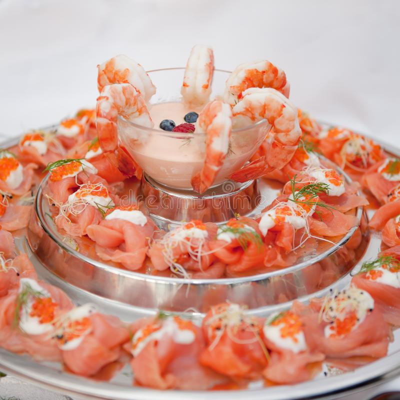 Prawns and salmon decorated with cocktail sauce and trout caviar on buffet stock photo