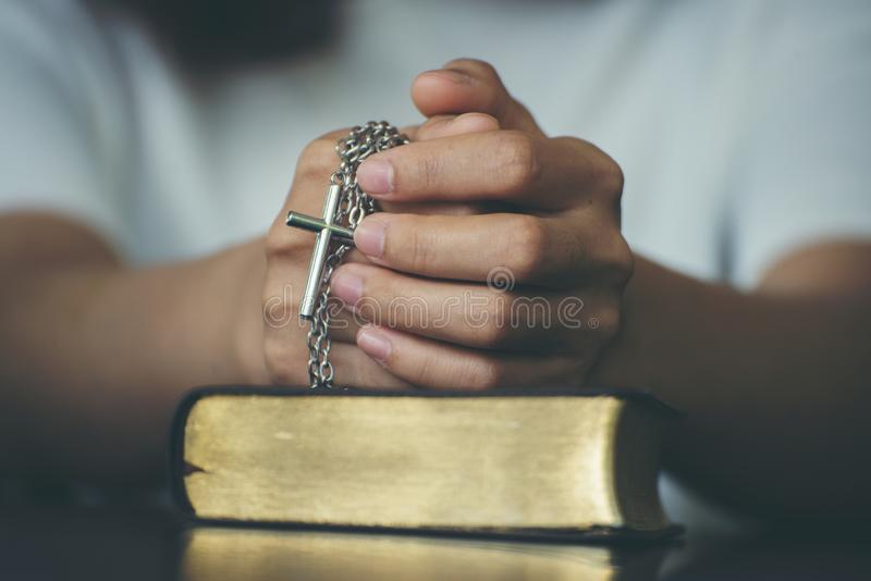 Pray and bible concept.Hand in hand together on bible by woman worship christian,thinking and closed her eyes at bed room.Person. Front view,Asian female stock images