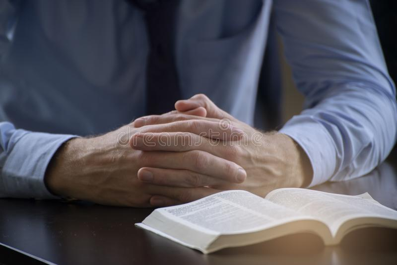 Pray and bible concept.Hand in hand together on bible by man worship christian,thinking and closed her eyes at bed room.Person. Front view,Asian male praying royalty free stock photography