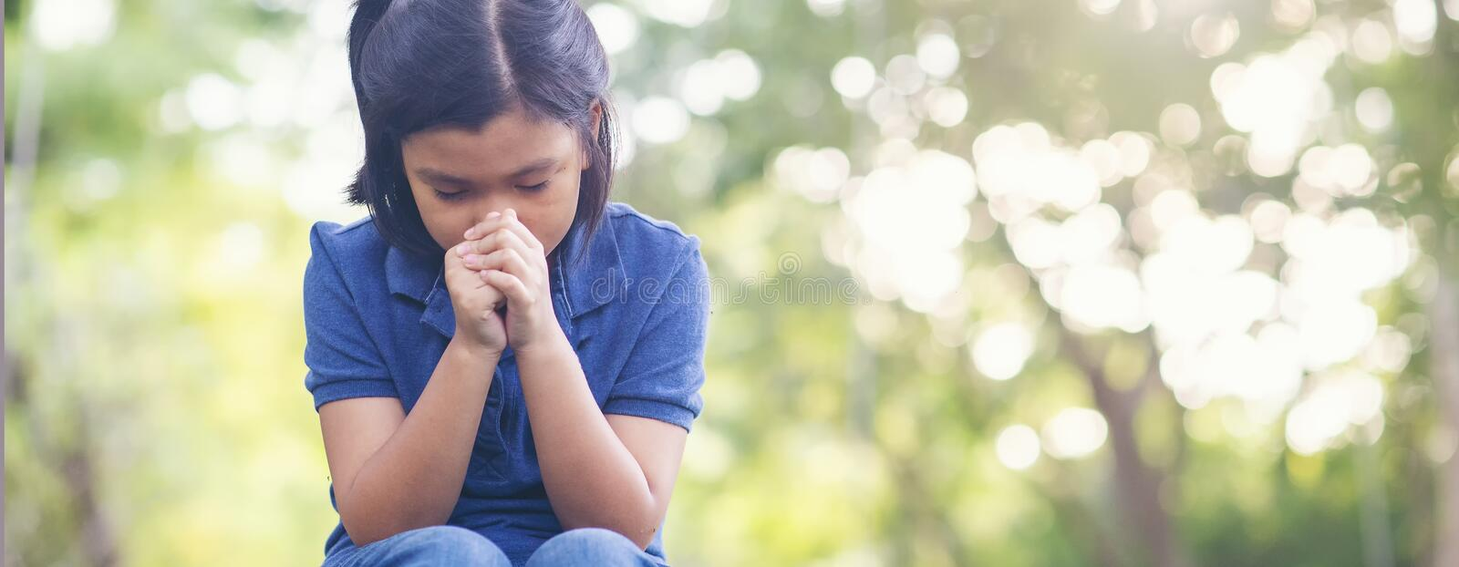 Pray concept. Asian child praying,hope for peace and free from disease,Hand in hand together by kid ,believes and faith in christian religion at church stock photo