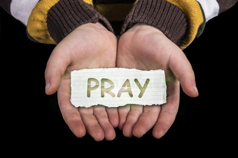 Pray text on hand. Pray text in line paper on child hand with glow isolated on black background royalty free stock image