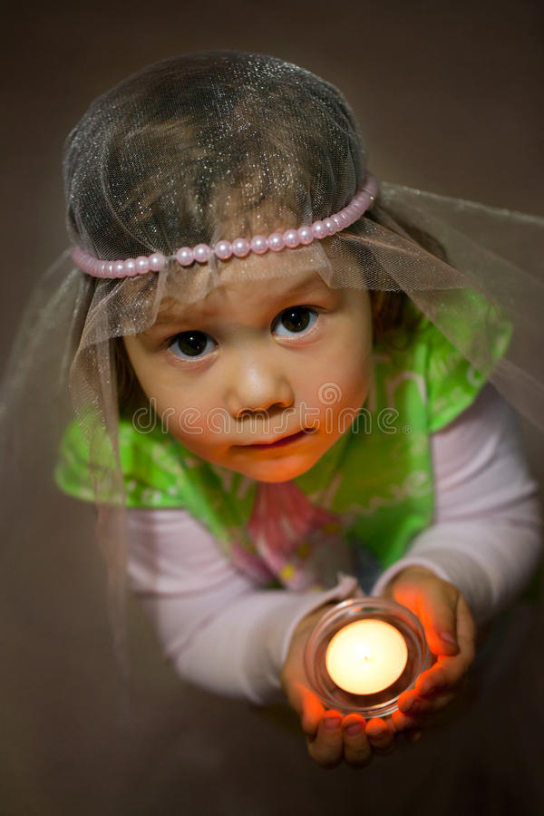 Prayer. Portrait of young girl with candle royalty free stock images
