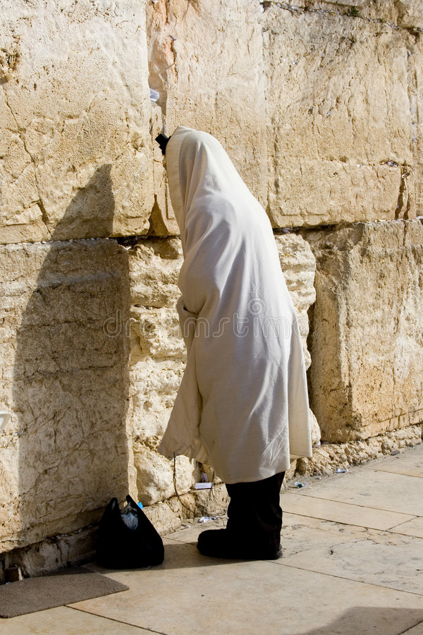 Prayer. A religious orthodox wearing a prayer shawl draped prays at the western wall. Jerusalem, Israel royalty free stock images