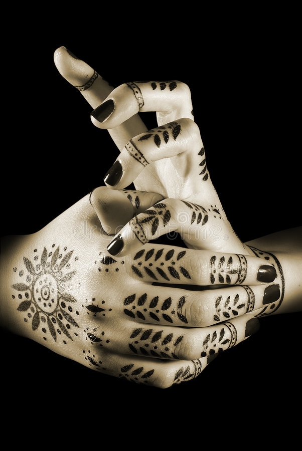 Prayer. Nice closeup woman's hands with oriental tattoo isolated over black stock image