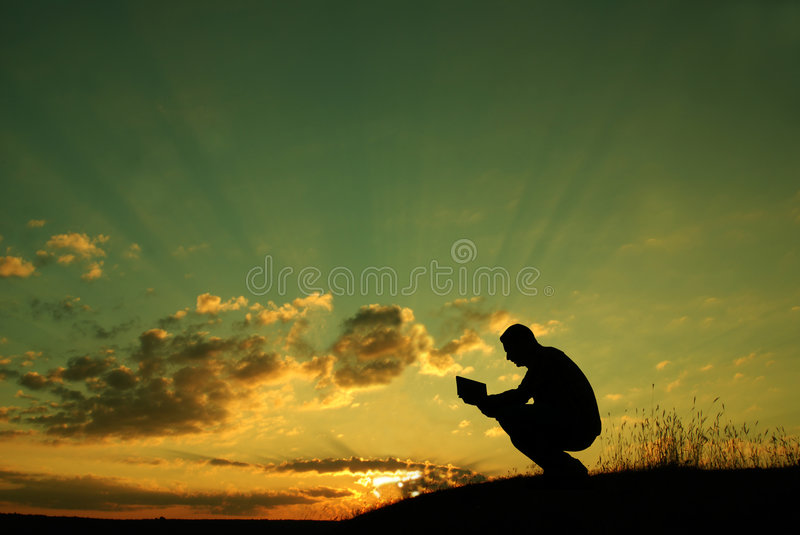 The prayer. A man holds the Holly Bible in his arms, making his morning prayer stock photo