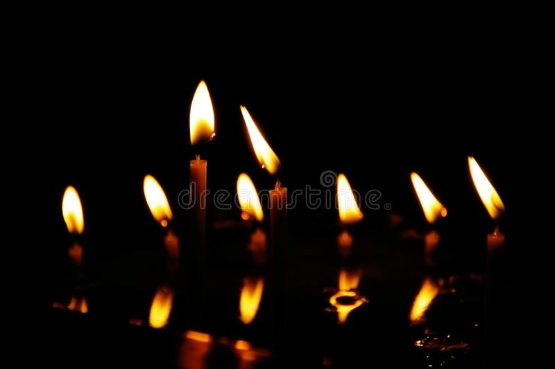 Prayer candles burning in silent darkness of temple, reflected in water stock photos