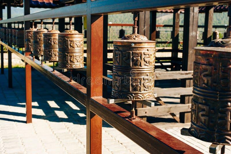 Prayer drum. Old prayer cylinders in Nepal. Tibetan Prayer wheels. Buddhist rolls in row stock photo