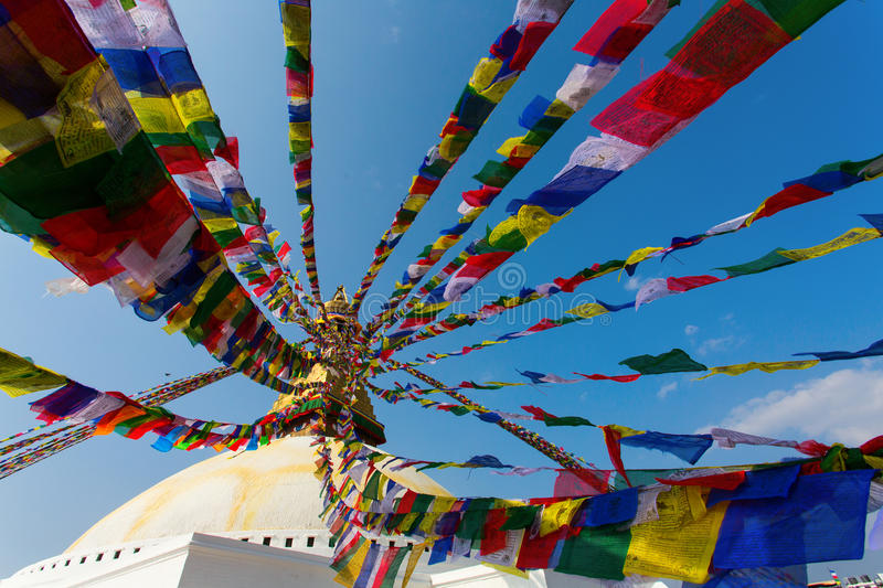 Prayer flags flying against the sun from the Boudhanath Stupa - symbol Kathmandu, Nepal.  royalty free stock images