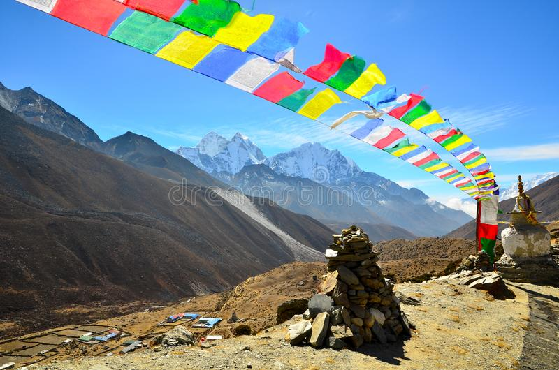 Prayer Flags Flying. Two strings of tibetan prayer flags flying in the wind with typical himalayan scenery in the background royalty free stock photos