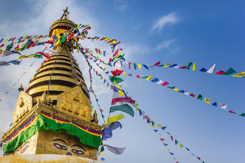 Prayer flags at the golden tower of the Swayambhunath stupa in Kathmandu. Nepal royalty free stock photography