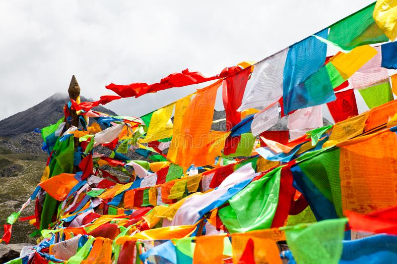 The prayer flags on the moutain on the way. Colorful flags with yellow blue green orange with tibetan Buddhist texts flow in the wind royalty free stock photo