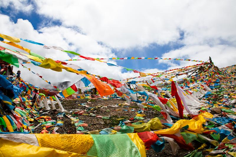 The prayer flags on the moutain on the way. Colorful flags with yellow blue green orange with tibetan Buddhist texts flow in the wind stock image