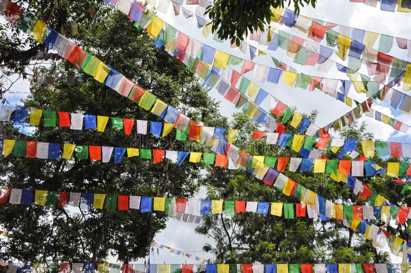 Prayer flags seen hanging ans flying in a hilly area in nepal royalty free stock photography