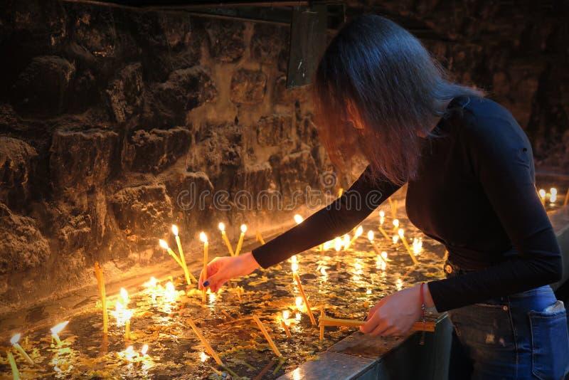 Prayer girl lights a candle and prays stock photos