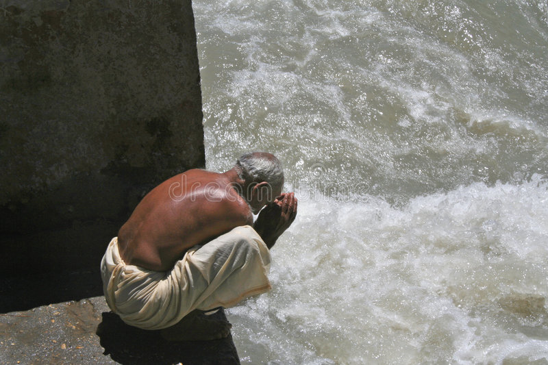 Prayer gratitude to life giving river Ganga India. Hindu man bows in prayer and gratitude to river Ganga the life source of many farmers and cities in the plains stock photography
