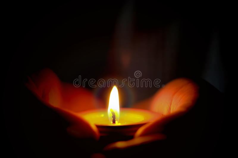 Prayer and hope concept of candle light in hands.