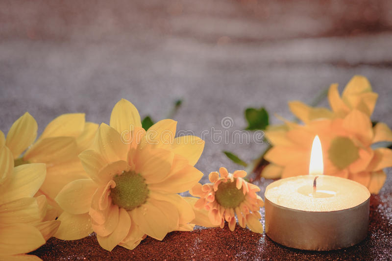 Prayer and hope concept. Retro candle light and yellow flower with lighting effect and glitter abstract background with bokeh defo royalty free stock images