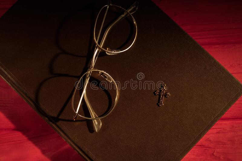 Prayer`s belongings concept. Closed holy bible book, glasses and shiny golden cross, top view royalty free stock images