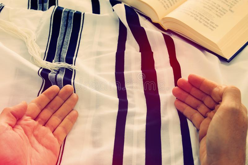 Prayer Shawl - Tallit and Prayer book jewish religious symbols. Jewish man hands holding a Prayer book, praying, next to tallit. Jewish traditional symbols. Rosh royalty free stock photo