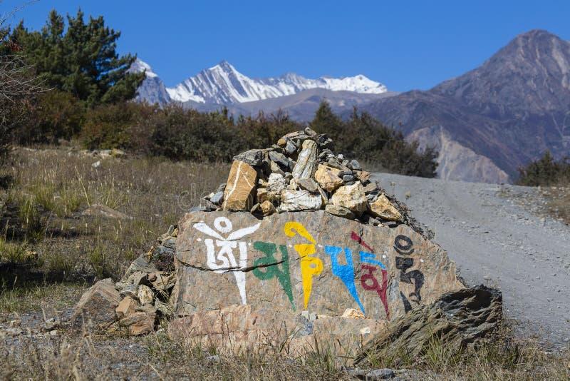 Prayer stones in Tibetan Buddhism, on the hill in Himalaya mountains. Annapurna region, Nepal royalty free stock photo