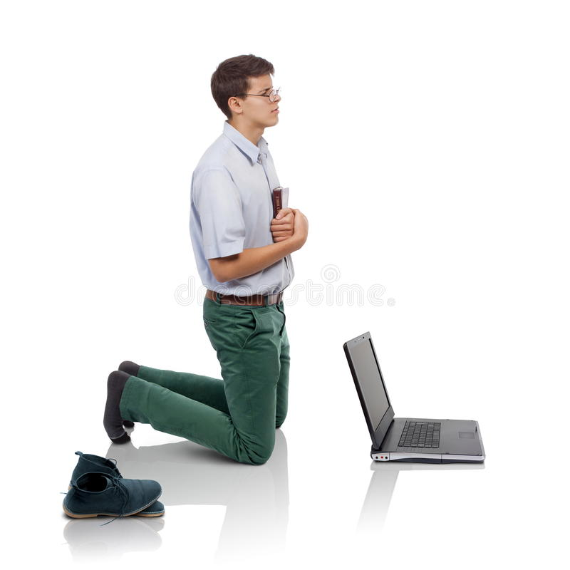 Prayer time. Young man knelt for prayer with the Bible in hand behind a laptop (Concept for prayer time or for breaking from the worldly things or fighting royalty free stock photography