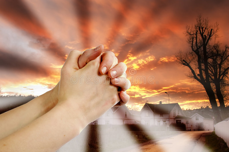 Prayer Warrior. Hands praying with a dramatic red sky overa small town; prayer warrior